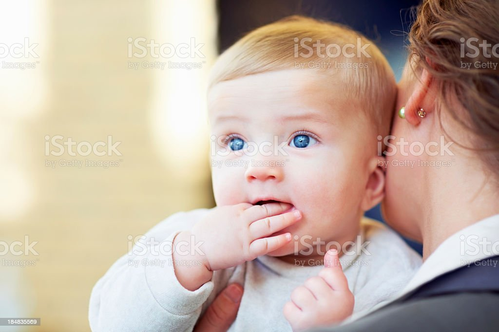 Blue eyed toddler being held by mother royalty-free stock photo