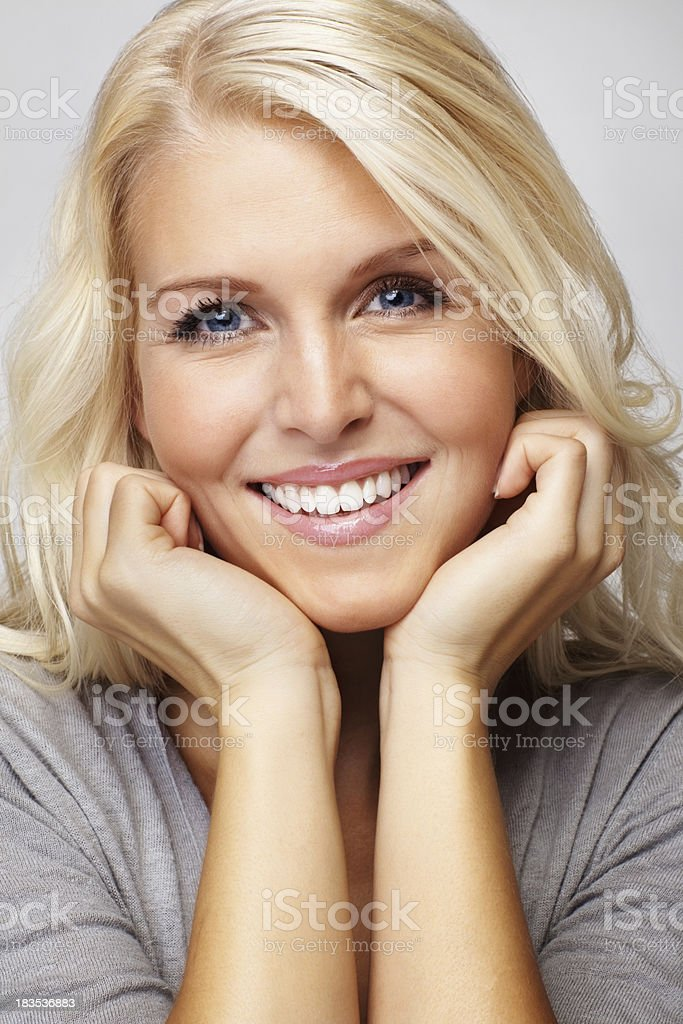 Blue eyed woman with hands on chin royalty-free stock photo