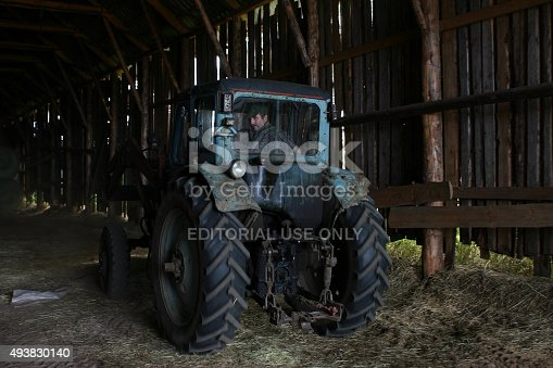istock Blue farm tractor with tractor driver, under roof of hayloft. 493830140