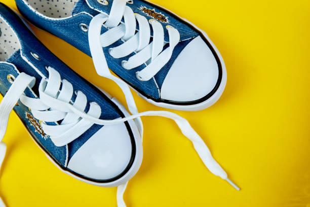 Blau weiblich oder männlich Turnschuhe auf gelbem Papierhintergrund. – Foto