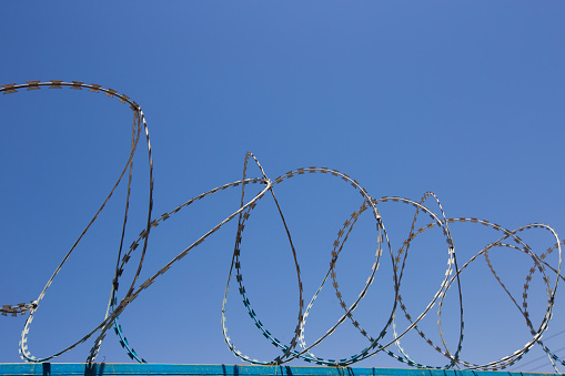 Blue Fence Made Of Wire With Spikes On Top Stock Photo