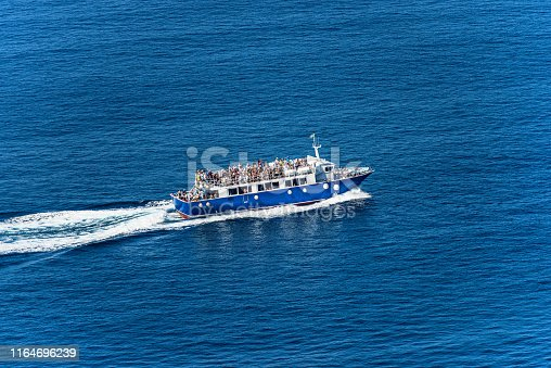 Blue ferry boat with many tourists during sailing to the Cinque Terre in the Mediterranean Sea. Gulf of La Spezia, Liguria, Italy, Europe
