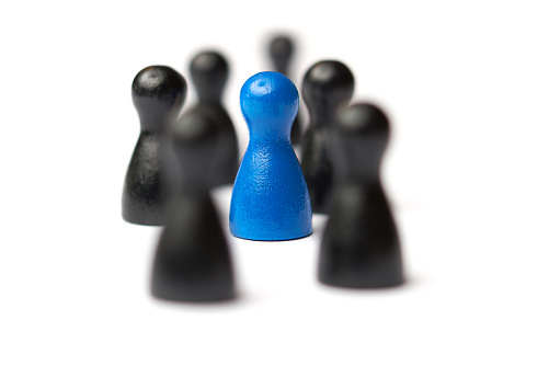 istock Blue figure in the middle of a group. Other figures blurred. Business concept for leadership, teamwork or groups. Isolated on white background. 814582842