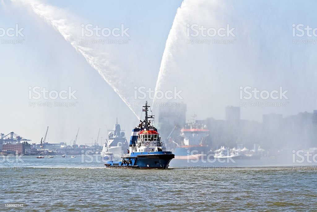 Blue fire boat spraying water in Rotterdam harbor Netherlands royalty-free stock photo