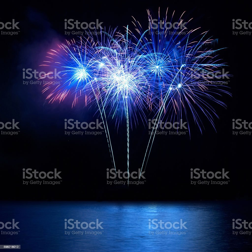 Blue fireworks above water stock photo