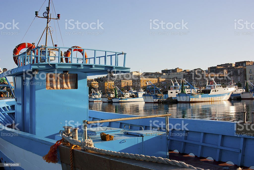 Blue fishing boat in the harbor stock photo