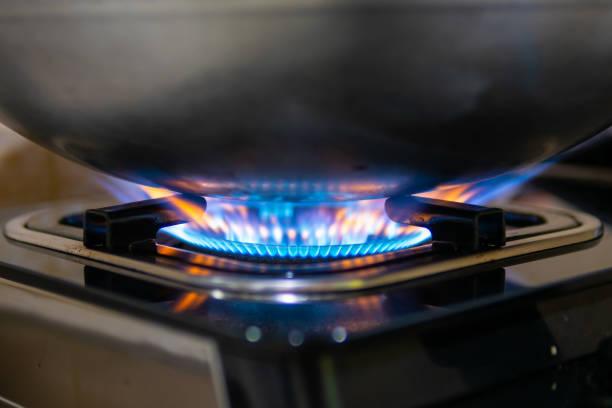 blauer flamme aus gas ofen heizung pfanne beim kochen essen - bratpfanne stock-fotos und bilder