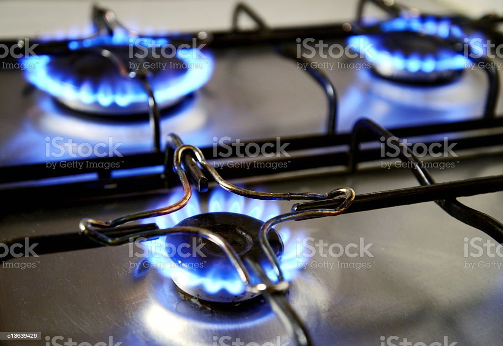 blue flames from gas stove stock photo