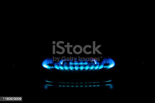 Blue flames of gas stove in the kitchen, Black background