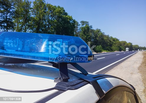 istock Blue flashing lights on the roof of a police car on the background of a high-speed road. Selective focus, close-up. 1017591308