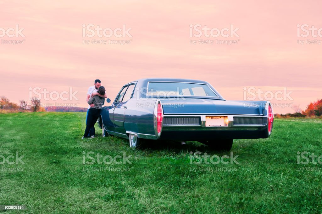 Blue Fleetwood Cadillac 1967 parked at sunset in a field stock photo