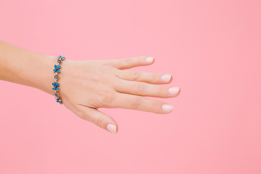 istock Blue flower bracelet on woman's wrist. Isolated on pastel pink background. Care about hand skin and nails. Closeup. 1126070370