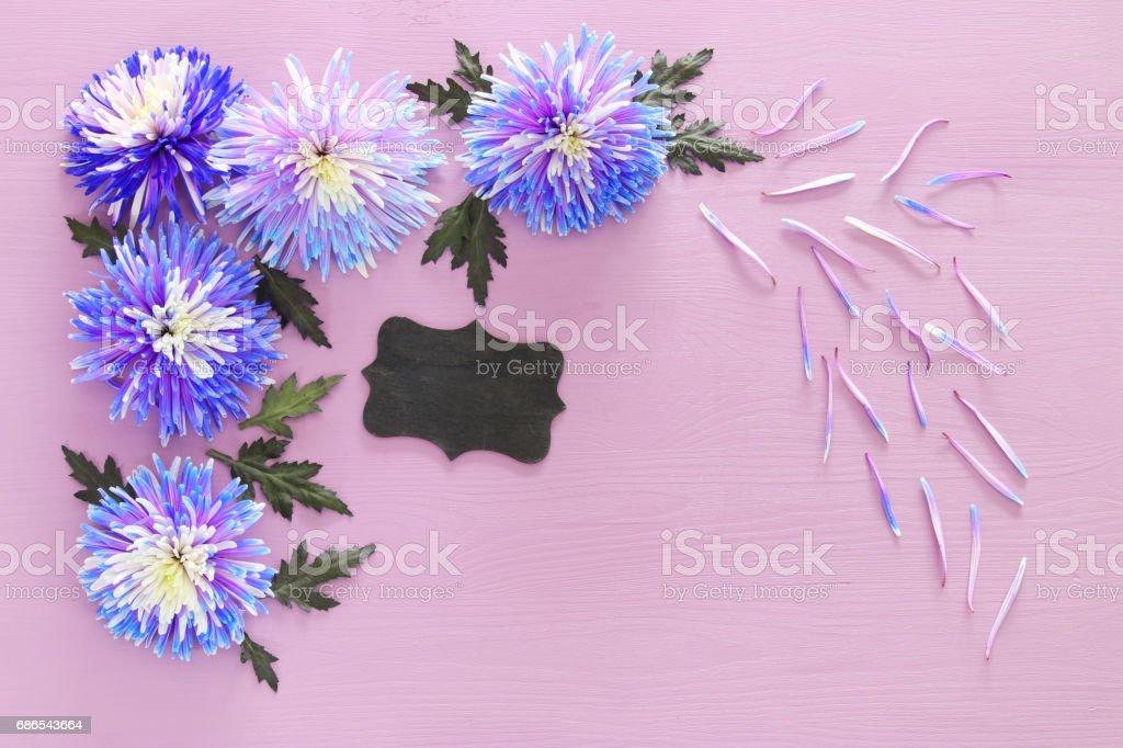 blå blommor arrangemang och blackboard på trä bakgrund royaltyfri bildbanksbilder