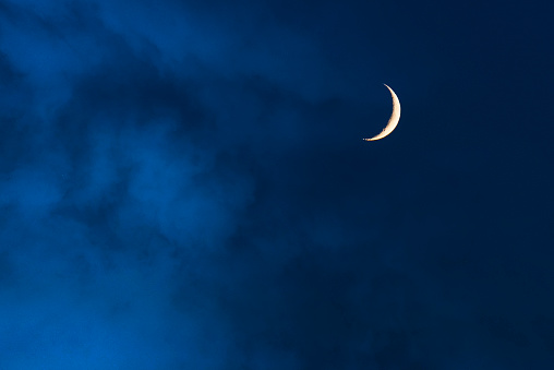 Blue foggy sky with crescent or half moon