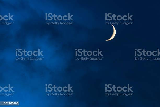 Photo of Blue foggy sky with crescent or half moon