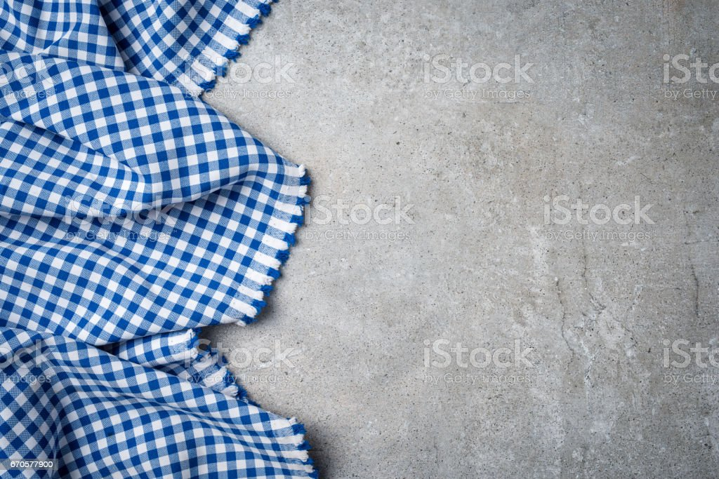 Blue folded tablecloth on gray stone table stock photo