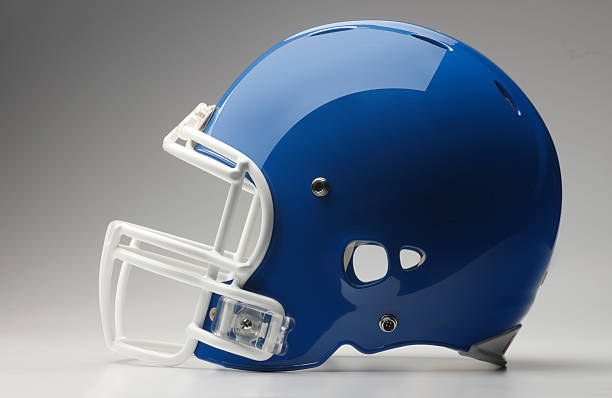 Blue Football Helmet A blue football helmet on a gray background. football helmet stock pictures, royalty-free photos & images