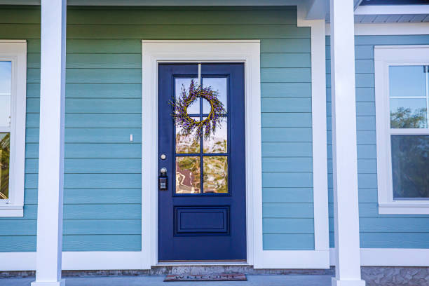 Blue Front Door of a brand new construction house with blue siding, a  ranch style home with a yard Blue front door of a brand new construction house with blue siding, a  ranch style home with a yard front door stock pictures, royalty-free photos & images