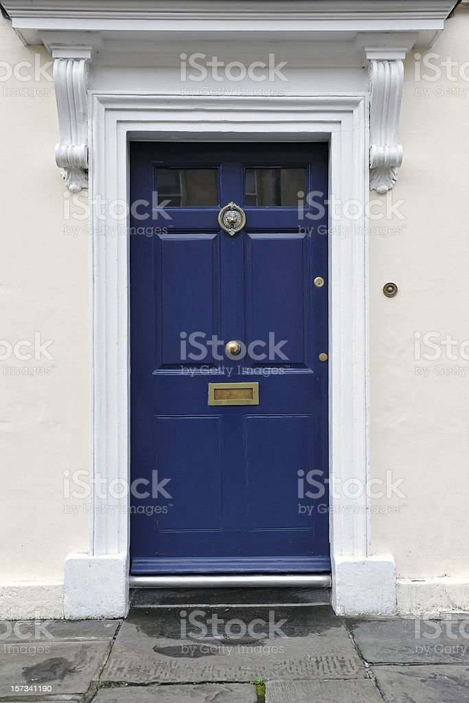 A blue front door on a white home stock photo