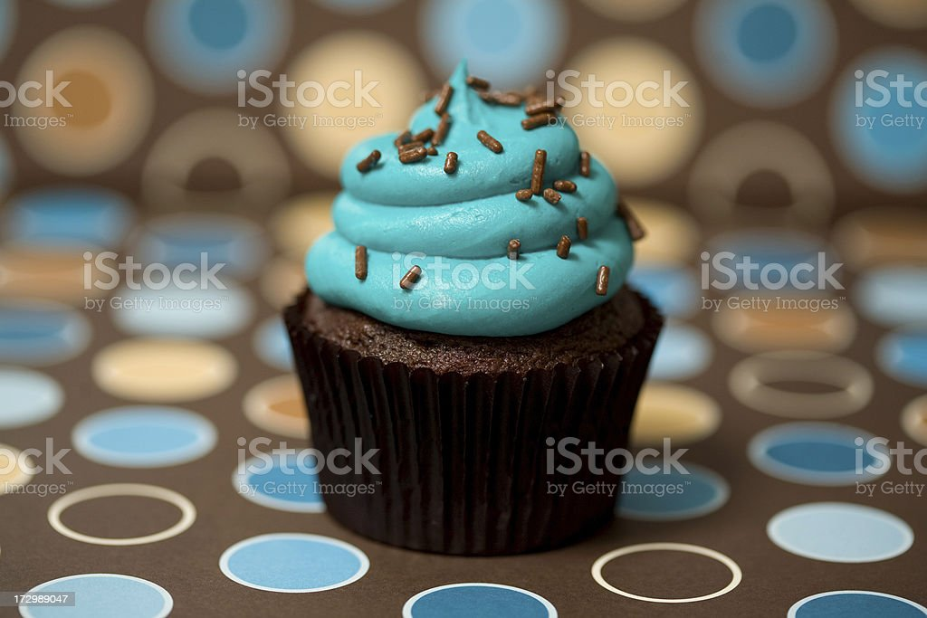 Blue frosted cupcake with a modern polka dot theme. royalty-free stock photo