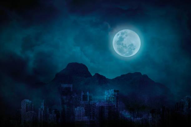 Blauer Vollmond in Der stadtverdankt mit den Bergen und Wolken, hell und dunkel um Mitternacht – Foto
