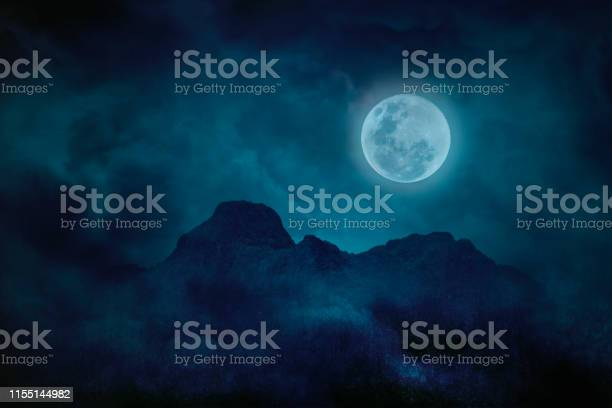 Photo of Blue full moon with mountains and forests in the darkness, Natural scary background