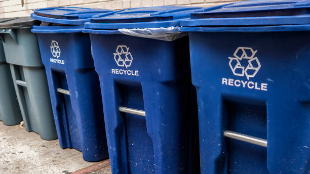 blue garbage bins with the white recycle logo - recycling bin stock photos and pictures