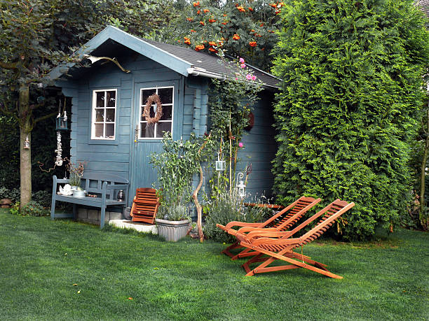 Blue garden shed with wooden lounge chairs stock photo