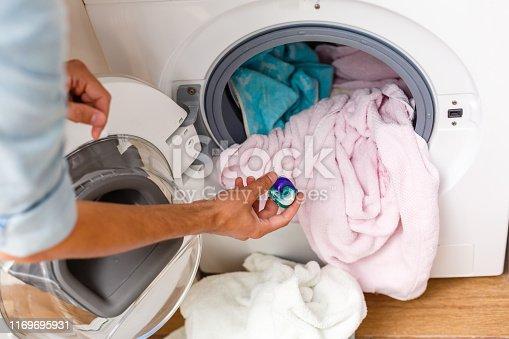 blue gel caps in hand for washing mashine, liquid coloured detergent