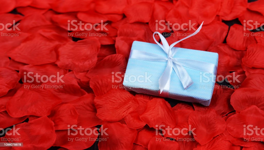 blue gift box with a bow surprise on the petals of red flowers with...
