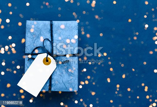 Blue gift box with white gift tag on blue background. Holiday concept. Copy space, top view. Color of the year 2020 classic blue toned.
