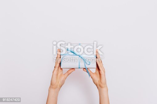istock Blue gift box with ribbon in female hands 915247420