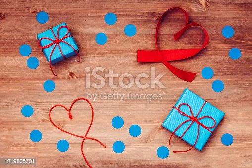 Happy fathers day words made of wooden blocks with blue gift boxes and red hearts on wooden background. Happy Father's day greeting card, holiday flat lay, top view, nobody