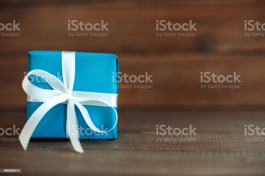 Blue gift with ribbon on a wooden background. Concept of holiday, birthday, Easter, March 8. royalty-free stock photo