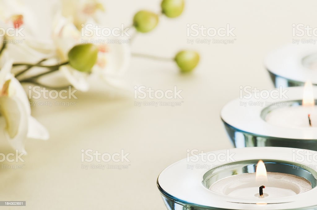 Blue glass candle holders with white orchid flower royalty-free stock photo