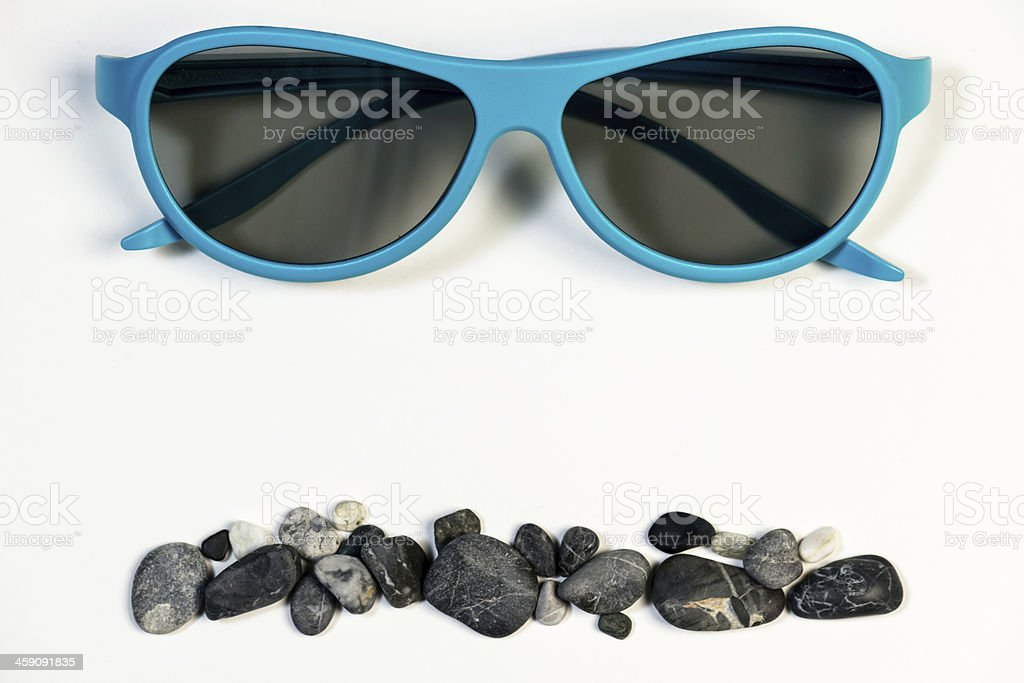 Blue glasses and small rocks royalty-free stock photo