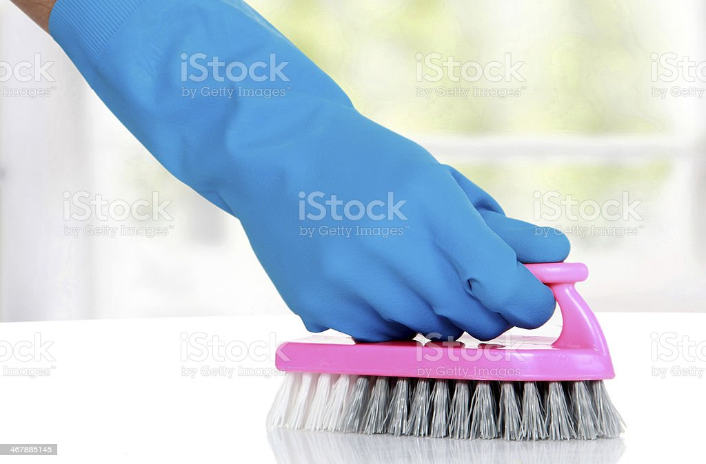 Blue gloved hand using a pink scrub brush on white surface stock photo
