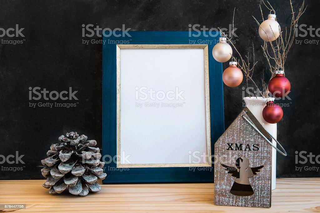 Blue Golden Frame Mock Up Christmas New Year Pine Cones Colorful Balls Candle Holder with Angel Figure Black Chalkboard Wall Blank Space for Quotes Lettering Text Minimalist Kinfolk Style stock photo