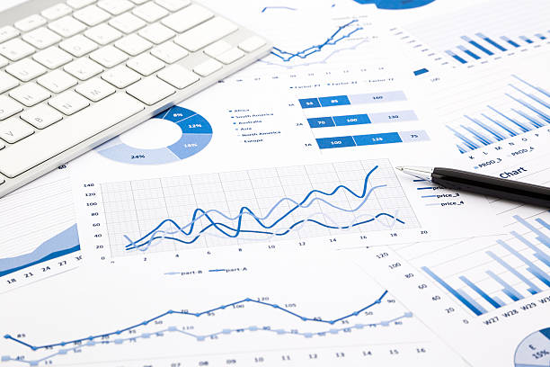 Blue graph and chart reports on office table stock photo