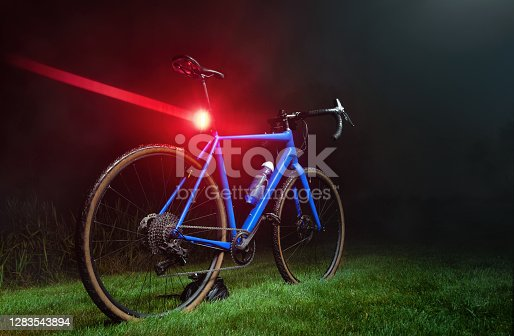Blue gravel bike with a bright red flashing light on a green lawn in the dark. Alternative to public transport.