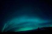 The aurora borealis radiates bright blues and greens in Iceland. The big dipper constellation can be seen in the sky