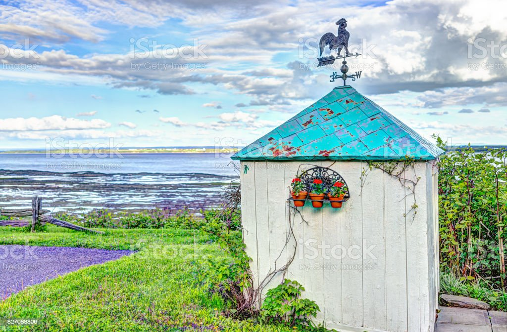 Blue green turquoise painted shed house with rooster compass on top in summer landscape French countryside by river stock photo