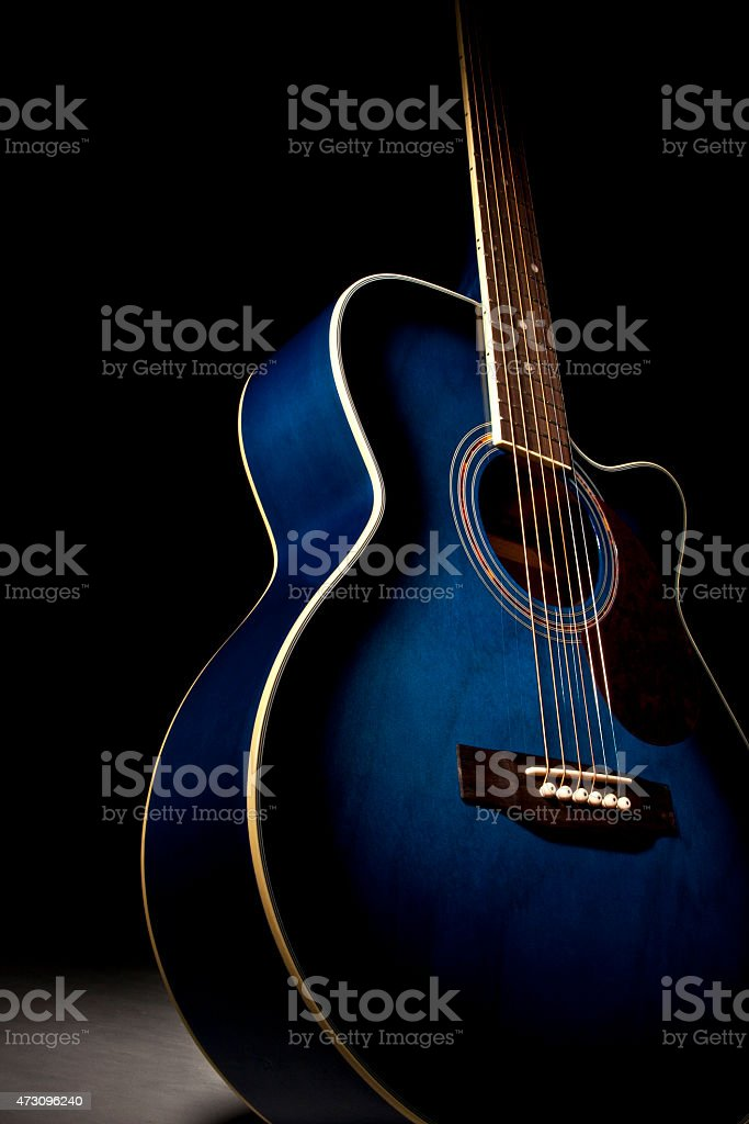 Blue guitar with dramatic lighting stock photo