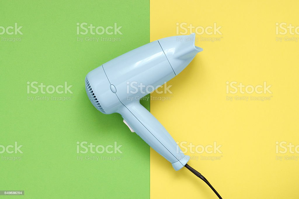 Blue hair dryer on green and yellow background – Foto