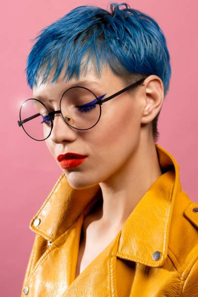 blaue haare mädchen in runde brille tragen gelbe jacke - blaues augen make up stock-fotos und bilder