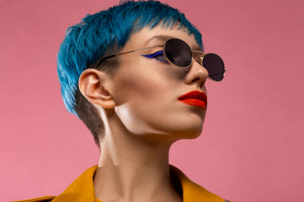 Blue hair girl in sunglasses wearing yellow jacket Blue hair girl in sunglasses wearing yellow jacket short hair stock pictures, royalty-free photos & images