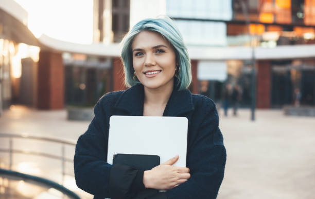 Blue haired charming woman posing outside embracing a computer and looking at joyfully at camera stock photo