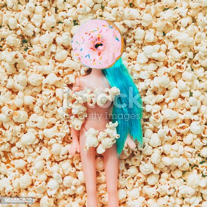 964258970 istock photo Blue haired plastic girl doll with a donut instead of a face on popcorn. 968882822