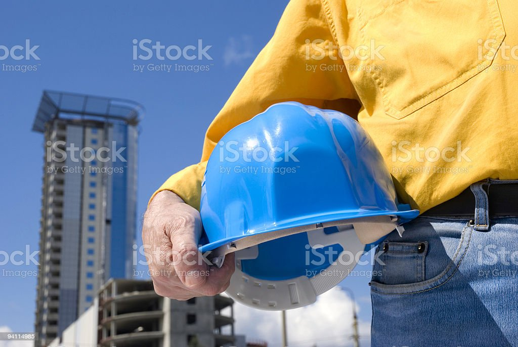 Blue Hard hat in construction workers hand, tall building royalty-free stock photo