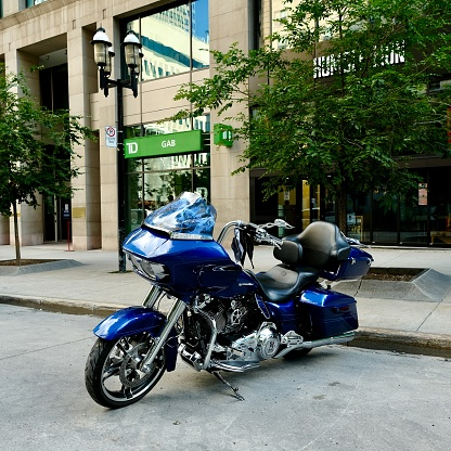 Montreal. Canada - Circa August 2020: Harley-Davidson motorcycle in blue is proudly parked at downtown Montreal.